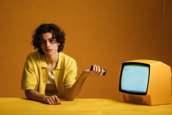 personne avec une télécommande devant une TV non segmentée